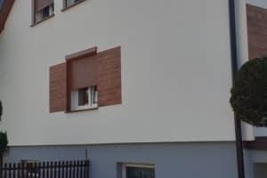 Dom z zewnątrz, okna z roletami, ogródek